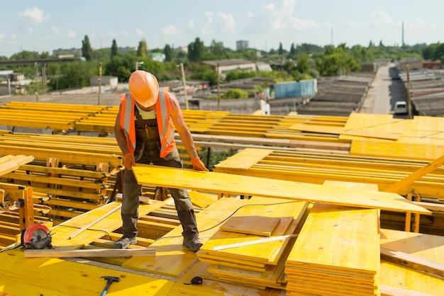 Рабочий в защитной каске собирает опалубку из деревянных панелей.