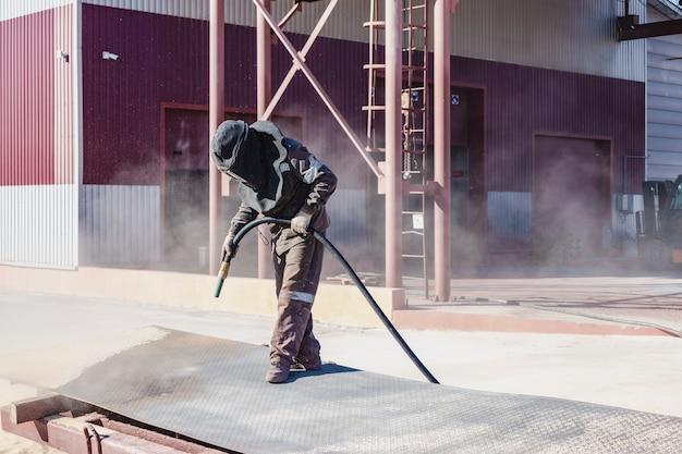 Рабочий в специальном костюме производит пескоструйную очистку металла на промышленной площадке.