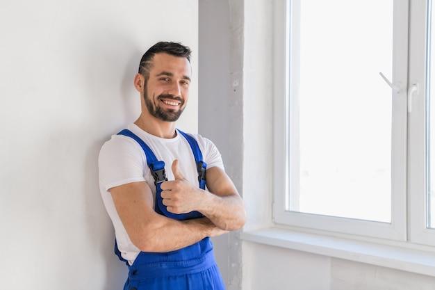 Рабочий в синей рабочей одежде стоит у стены и позирует