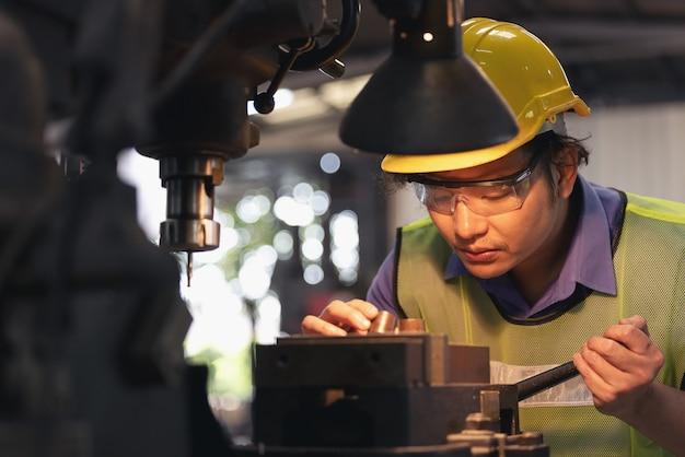 Рабочий в очках стоит возле промышленного оборудования и проверяет производство. человек работает на машине на заводе