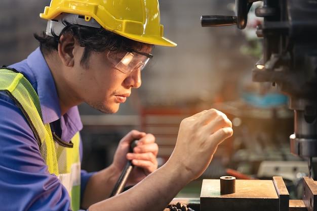 産業機器の近くに立って生産を確認する眼鏡の労働者。工場で機械を操作する人
