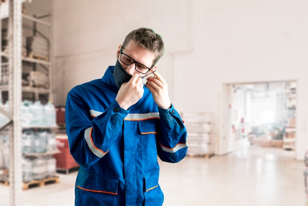 仕事をしながら保護マスクを着用している制服を着た労働者。コロナウイルスから保護する
