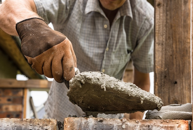 작업자가 벽돌에 흙손으로 모르타르를 바르고 있습니다.