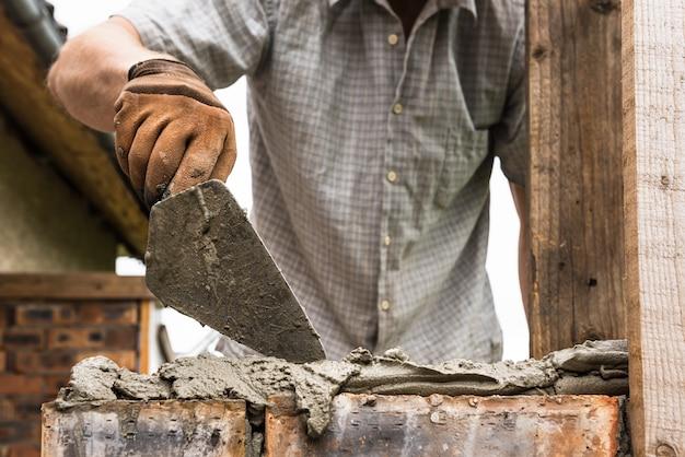 Рабочий наносит кельмой раствор на кирпич.