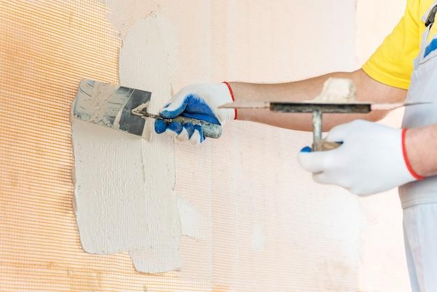 Рабочий наносит шпаклевку на сетку из стекловолокна на стене.
