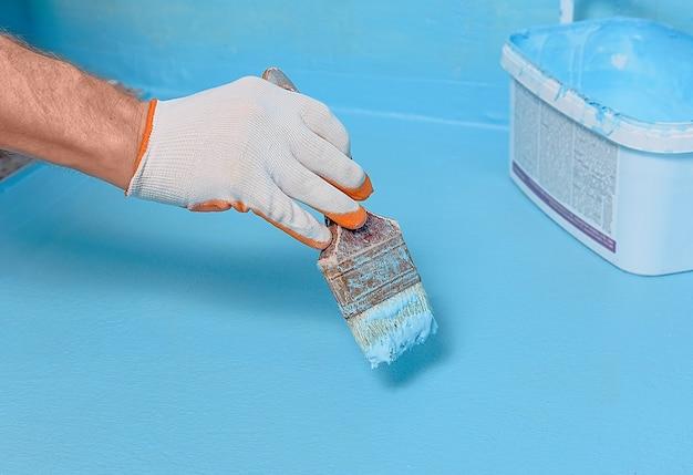 Рабочий наносит гидроизоляционную краску на пол в ванной