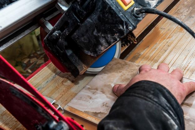 작업자가 습식 절단기 톱 기계에서 세라믹 타일을 절단하고 있습니다