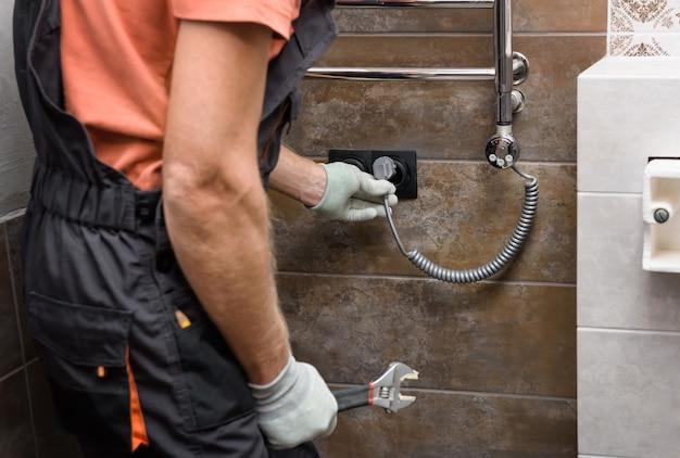 작업자가 욕실의 수건 보온기에 발열체를 설치하고 있습니다.