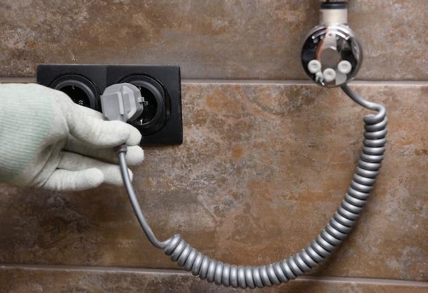 Рабочий устанавливает нагревательный элемент в полотенцесушитель в ванной.