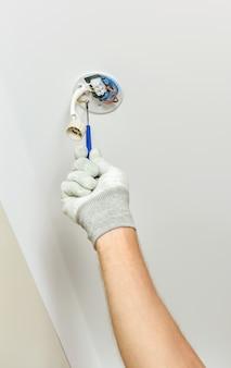 Рабочий устанавливает на подвесной потолок точечный светодиодный светильник.
