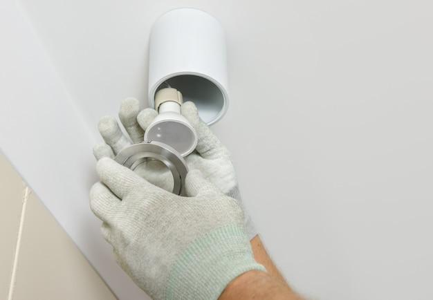Рабочий устанавливает светодиодный точечный светильник на подвесной потолок.