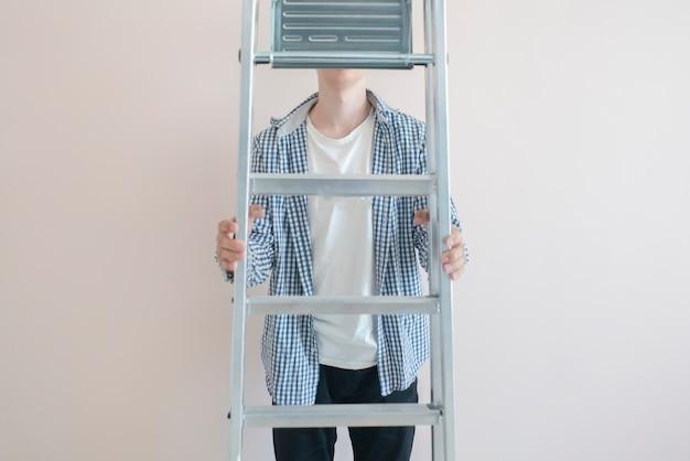 새 집의 벽에 알루미늄 사다리를 들고 노동자 남자 프리미엄 사진