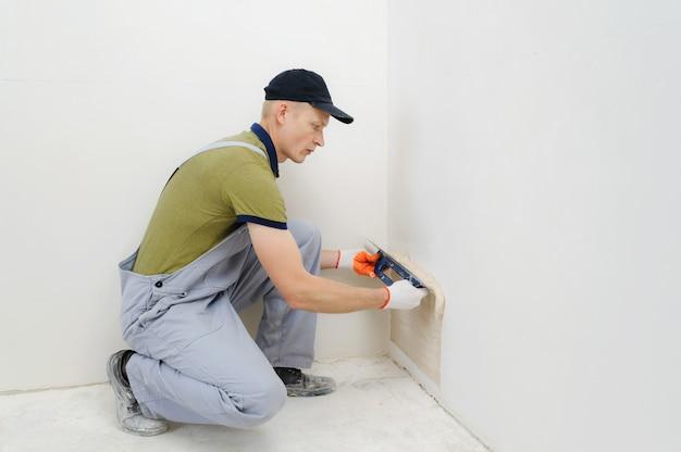 Рабочий штукатурит стену.