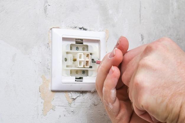 Рабочий снимает выключатель света для оклейки обоев.