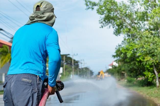 Работник распыления воды, чтобы очистить дорогу с напорной системой водоснабжения, влажной уборкой улицы.