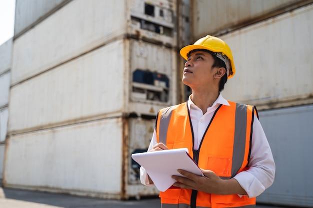 Рабочий, стоящий и одетый в желтый шлем, контролирует погрузку и проверяет качество контейнеров с грузового грузового судна для отправки на импорт и экспорт. Premium Фотографии