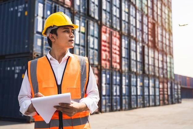 Рабочий, стоящий и одетый в желтый шлем, контролирует погрузку и проверяет качество контейнеров с грузового грузового судна для отправки на импорт и экспорт.
