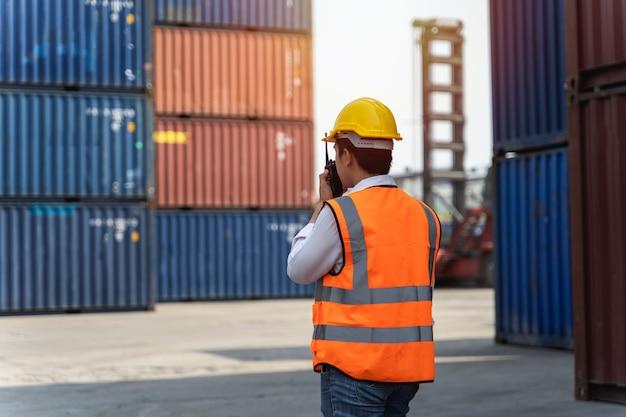 Рабочий, стоящий и одетый в желтый шлем, контролирует погрузку и проверяет качество контейнеров с грузового грузового судна для перевозки импорта и экспорта