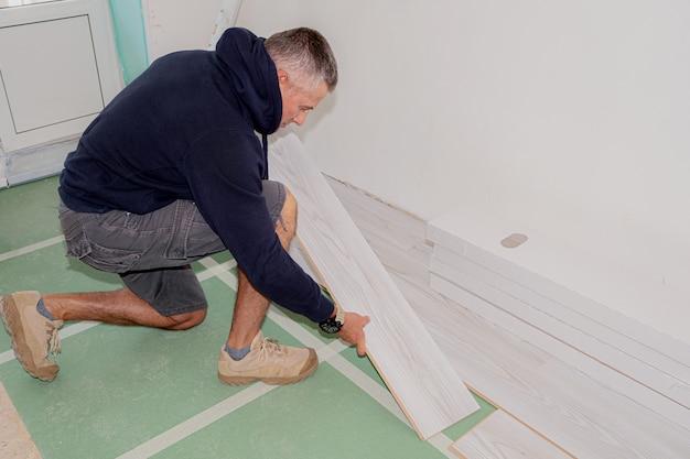 Рабочий, соединяющий ламинат во время ремонта дома.