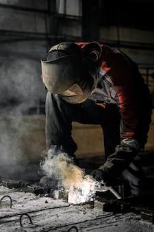 보호 마스크를 착용 한 작업자가 용접기를 사용하여 금속을 용접하고 있습니다.