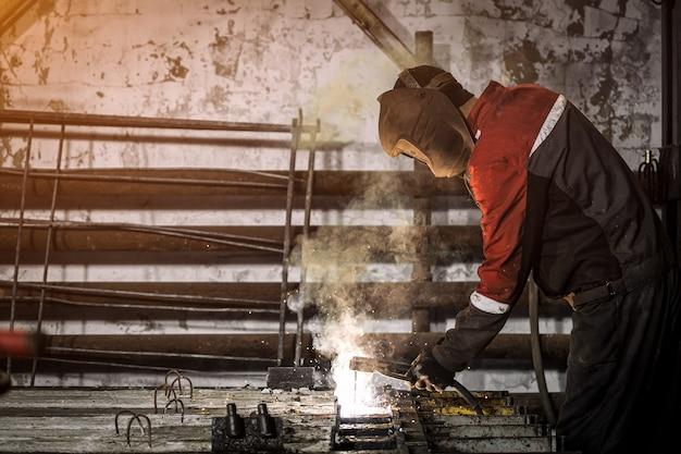 Рабочий в защитной маске сваривает металл с помощью сварочного аппарата