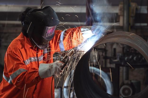 Рабочий с защитной маской сваривает металлическую трубу на заводе