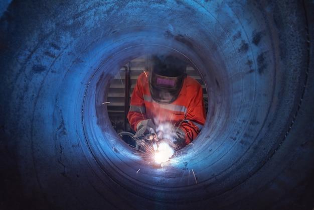 Рабочий с защитной маской сварочной стальной конструкции на заводе