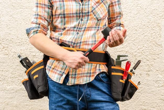 Рабочий с сумками для инструментов на поясе и резиновым молотком в руке.