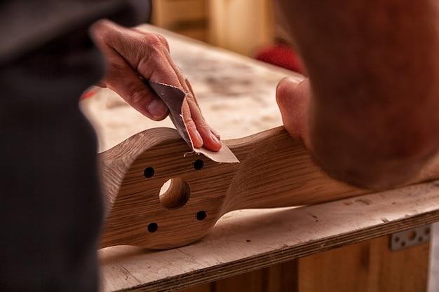 Рабочий в кепке и рубашке полирует деревянный брусок