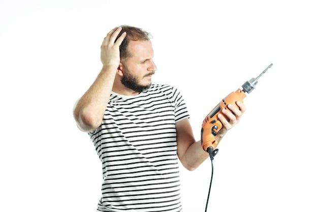 困惑している働く男性は、電動工具である電気ドリルを見て考えました。白で隔離。