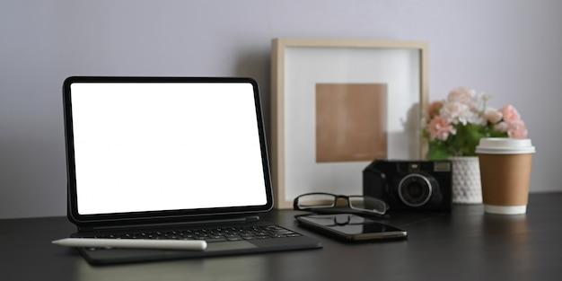 작업 공간은 흰색 빈 화면 컴퓨터 태블릿 및 개인 장비로 둘러싸여 있습니다.