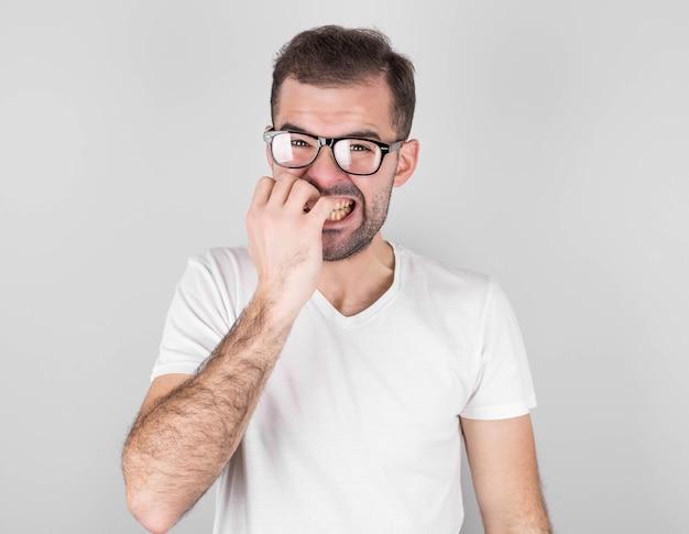 걱정스러운 힙 스터 남자가 손톱을 물어 뜯고 시험을 보거나 인생에서 중요한 사건을보기 전에 긴장합니다. 어려움을 두려워하는 당황한 유행 젊은이 회색 벽에 서