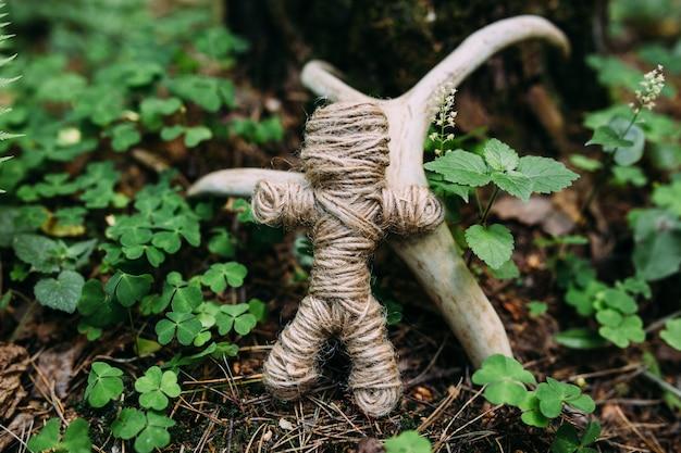 Плетеная кукла вуду из ниток и костей в ритуале в таинственном лесу