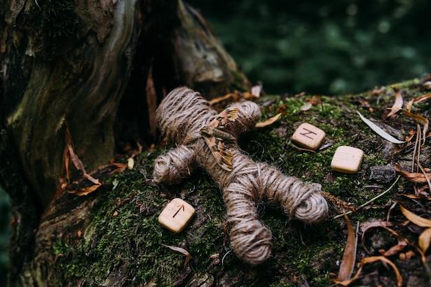 Плетеная кукла вуду из ниток мотылька и рун в ритуале в таинственном лесу