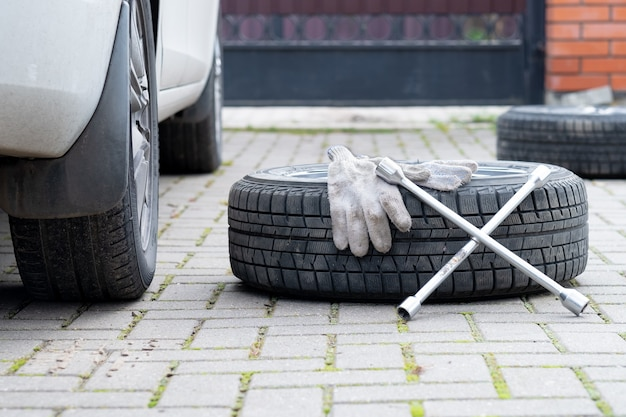 レンチと作業用手袋は、地面に横たわっている冬の車の車輪の上にあります