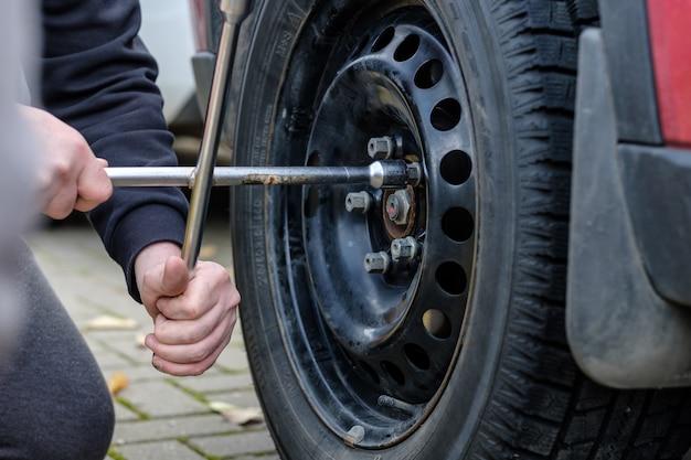 자동차 정비사의 손에 있는 렌치는 가을날 자동차 바퀴의 볼트와 너트를 풉니다