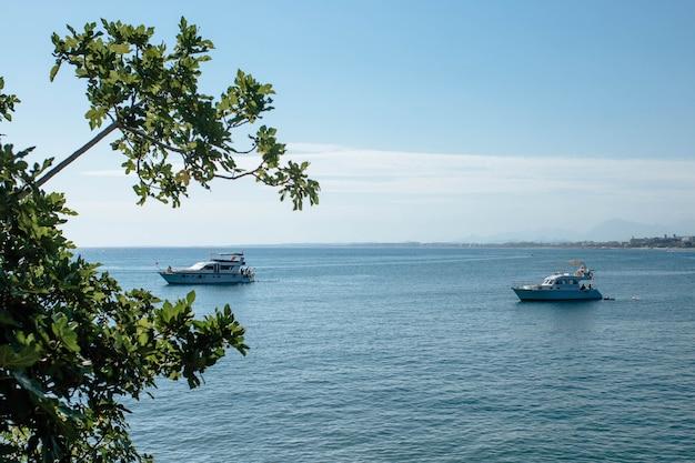 Яхта с туристами стоит в бухте для купания. красивое небо где-то вдалеке летит парашют и спокойное море безрогого окраса.