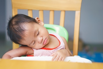 A year and 3 months Asian baby is sleeping while eating
