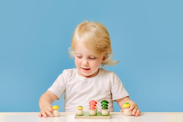 한 살짜리 아이가 파란 배경에 화려한 교육 장난감을 가지고 탁자에서 놀고 있다