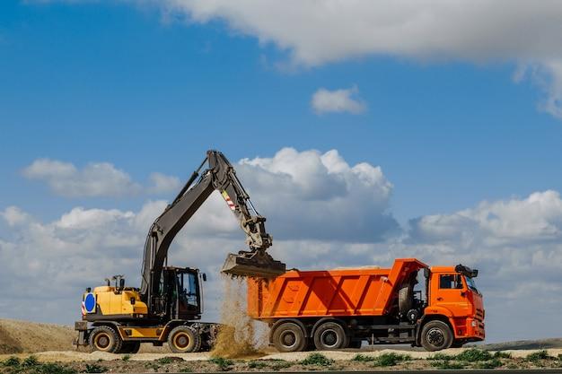 空を背景にした道路の建設中に、黄色のバックホウローダーが地球をトラックに積み込みます