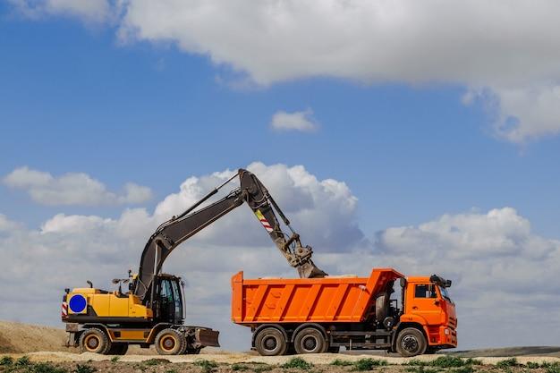 Желтый экскаватор-погрузчик загружает землю в грузовик во время строительства дороги.