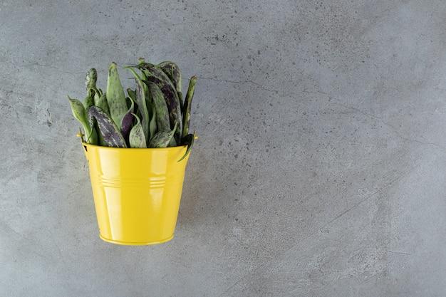 灰色の背景に未調理のエンドウ豆と黄色のバケツ。高品質の写真