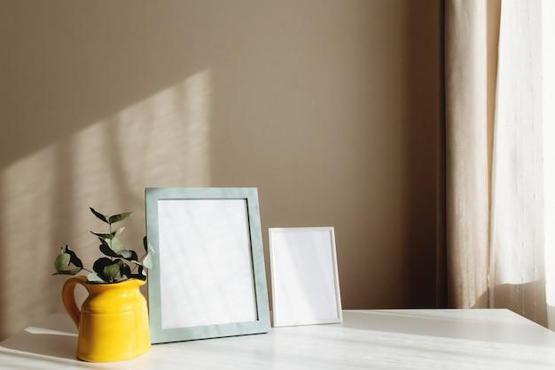 Желтый керамический кувшин или ваза с ветвями эвкалипта, пустые белые рамки для фотографий на белом столе в интерьере с бежевыми стенами у окна.