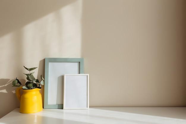 ユーカリの枝が付いた黄色のセラミックの水差しまたは花瓶、窓の近くにベージュの壁がある内部の白いテーブルに空の白いフォトフレーム。