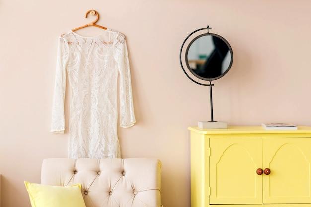노란색 서랍장, 안락 의자, 거울은 베이지 색 벽 배경에 서 있습니다. 가로 사진