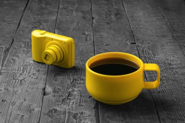 木製のテーブルに黄色いコーヒーカップと黄色いカメラ。創造的な朝食。