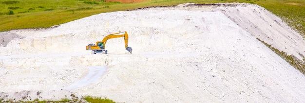 노란색 굴착기는 여름날 노천 구덩이에서 돌 분필을 파냅니다. 와이드스크린 이미지. 배너.