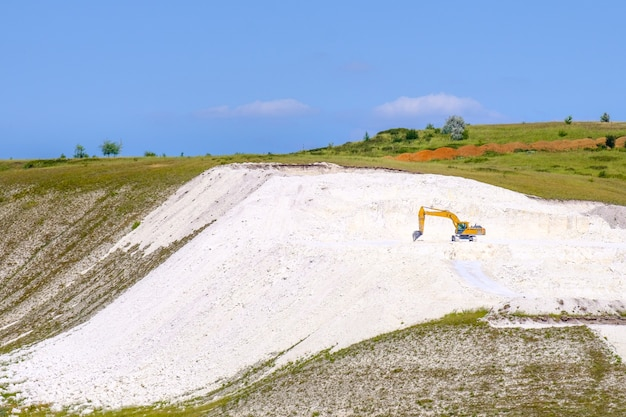 노란색 굴착기는 여름날 노천 구덩이에서 돌 분필을 파냅니다.