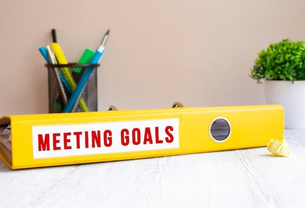 Meetinggoalsというラベルの付いた黄色のフォルダーがオフィスの机の上にあります。花と文房具の背景。