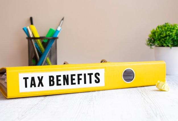Taxbenefitsというラベルの付いた黄色のフォルダーがオフィスの机の上にあります。花と文房具の背景。財務コンセプト。